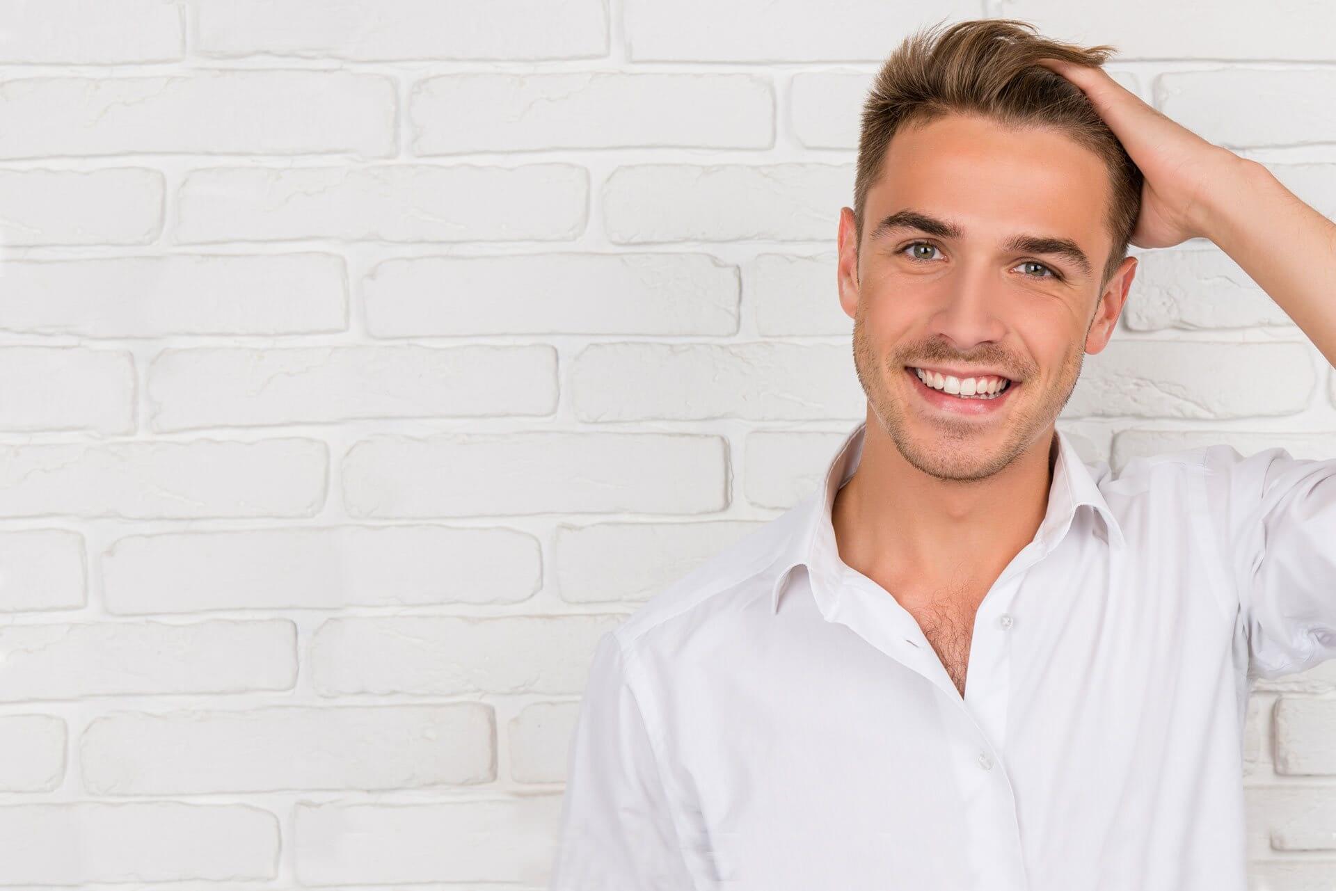 Hombre sonriendo y tocándose el pelo