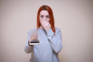 Mujer preocupada por caída de cabello